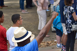 An attendee in the crowd raises his fist during the National Anthem at an event with President Barack Obama as he stumps in support of Democratic Presidential candidate Hillary Clinton at a September 13, 2016 rally at the foot of the Art Museum Steps in Philadelphia, Pennsylvania.