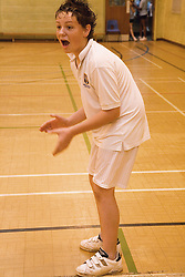 Secondary school student cheering on his team mates during a game of indoor cricket in the school sports hall,