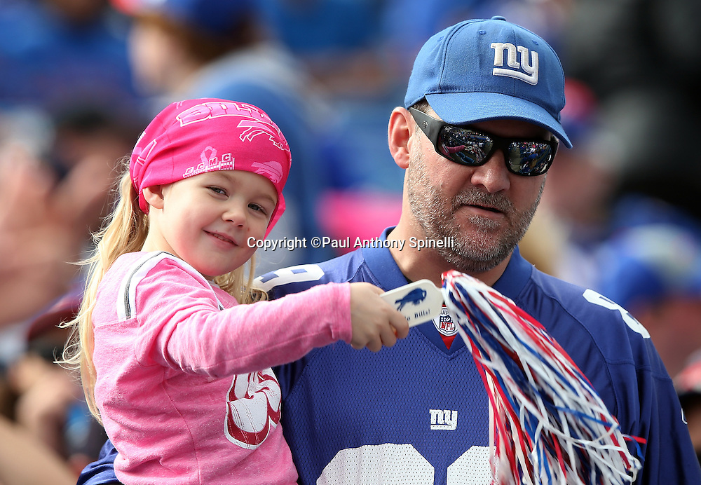 A New York Giants fan wears a pink outfit in tribute to breast cancer awareness month as she waves a pom pom while being carried down to her seat during the New York Giants 2015 NFL week 4 regular season football game against the Buffalo Bills on Sunday, Oct. 4, 2015 in Orchard Park, N.Y. The Giants won the game 24-10. (©Paul Anthony Spinelli)