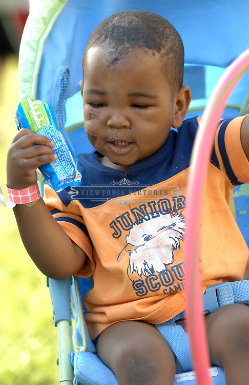 Karter Matthews, 1, plays with a hula hoop outside the Belk Activity Center, which is serving as a shelter in Tuscaloosa, Alabama, Saturday, April 30, 2011. The siblings' parents' home in the Alberta City neighborhood of Tuscaloosa was destroyed in the April 27 tornado.  Karter sustained facial injuries in the storm and his mother was hospitalized with a broken foot.  Their father Keith Matthews is taking care of him and his sisters, three-year old Khloe Matthews and  10-month old Krystin Matthews while they stay at the shelter.Tuscaloosa, Alabama, Saturday, April 30, 2011. Tornado Damage in Alabama 2011