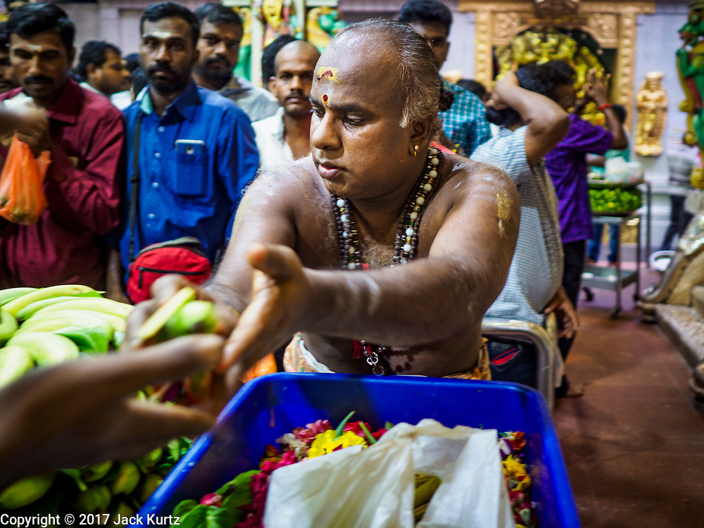 "09 JULY 2017 - SINGAPORE:  A Hindu priest hands out bananas that have been blessed in Sri Veeramakaliamman Temple in Singapore's ""Little India."" There are hundreds of thousands of guest workers from the Indian sub-continent in Singapore. Most work 5 ½ to six days per week. On Sundays, the normal day off, they come into Singapore's ""Little India"" neighborhood to eat, drink, send money home, go to doctors and dentists and socialize. Most of the workers live in dormitory style housing far from central Singapore and Sunday is the only day they have away from their job sites. Most work in blue collar fields, like construction or as laborers.   PHOTO BY JACK KURTZ"