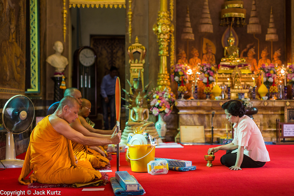 15 JULY 2014 - BANGKOK, THAILAND:   Buddhist monks and a woman participate in a religious service in the ubosot (ordination hall) at Wat Rachathiwat Ratchaworawihan on Samsen Soi 9. The temple has a large teak instruction hall, considered one of the finest teak buildings in Asia.   PHOTO BY JACK KURTZ