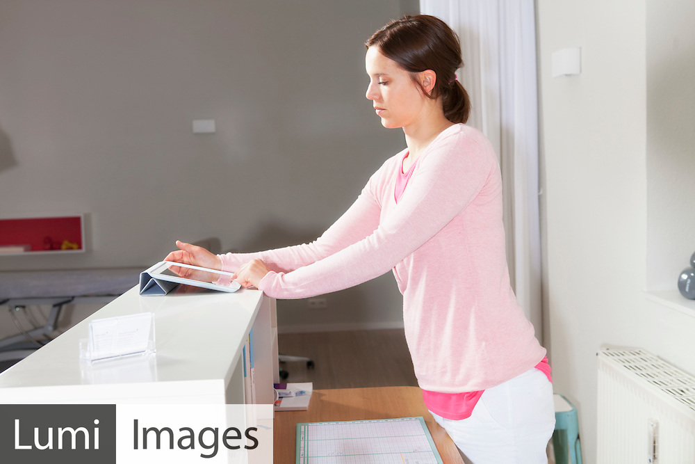 Female receptionist at check-in counter in an physiotherapy practice, Munich, Bavaria, Germany