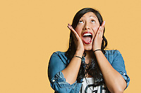 Surprised young woman with head in hands looking up over colored background