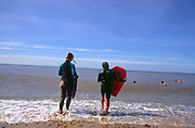 AJDM7F Two childen in black wet suits body boarding sea