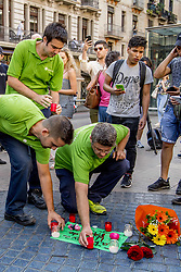 People lay flowers and candlelights in Las Ramblas avenue a day after a deadly van attack in Barcelona, northeasten Spain, August 18, 2017. At least 13 people died and some 100 were injured when a van crashed into pedestrian. Photo by Robin Utrecht/ABACAPRESS.COM