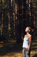 Worried woman standing in woods looking up at canopy