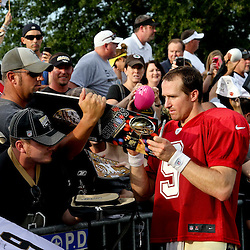 July 28, 2012; Metairie, LA, USA; New Orleans Saints quarterback Drew Brees (9) signs autographs following a training camp practice at the team's practice facility. Mandatory Credit: Derick E. Hingle-US PRESSWIRE