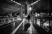 Shade of a person walking on the Brooklyn Bridge at night