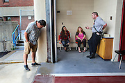 Kelly Hogan, left, of Milton Mills NH, looks down at his<br /> feet as EMS officer/firefighter paramedic Chris Hickey, right, talks with walk-in addicts, Hogan's daughter, Melissa Hogan, 33, 2nd from right, and her friend Natalie McNally, 33, 2nd from left, the two woman are looking for help at the Main Fire Station in Manchester, NH Wednesday, Aug. 10, 2016. <br /> To help combat Manchester New Hampshire's huge drug problem, anyone can walk into the main fire station seeking help, they'll get connected with a drug counselor and services. Something like 230 people have shown up in the first couple months and it's quickly spawning copy-cat programs.  <br />    (Cheryl Senter for The Wall Street Journal)