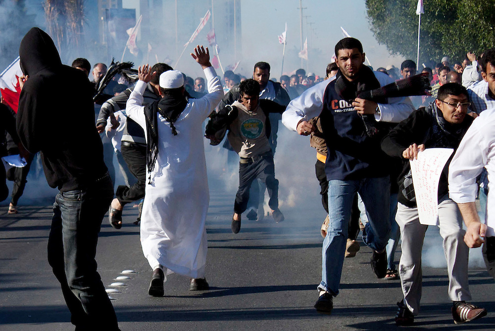 A man attempts to calm Bahraini protesters as they are fired upon by security forces during a march in Manama.