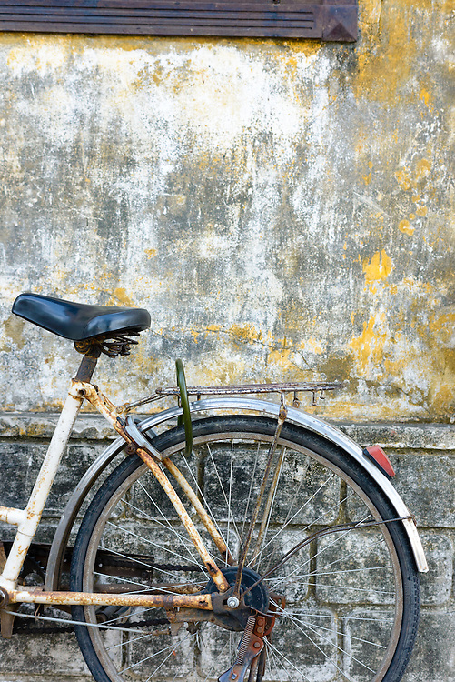 Worn bicycle leant against a delapidated wall in Hoi An Ancient Town