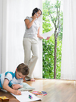 Mother using cell phone young son drawing on floor