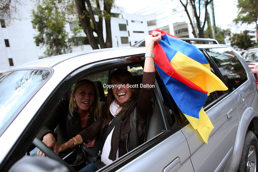 Two woman honk the car horn and wave a Colombian flag as they drive by the French Embassy where Ingrid Betancourt, who was help captive by FARC rebels for over 6 years before being rescued by the Colombian military, held a press conference in Bogotá on July 3, 2008. (Photo/Scott Dalton).