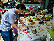 """05 SEPTEMBER 2017 - BANGKOK, THAILAND: A man sets up his family's Hungry Ghost Day banquets in Bangkok's Chinatown. The Ghost Festival is a Buddhist and Taoist holy day celebrated on the 15th day of the 7th lunar month. It is primarily celebrated in China and Chinese communities outisde China. In Thailand, it's celebrated in Thai-Chinese communities in Bangkok, Phuket and Chiang Mai.  On that day ghosts and spirits, including those of the deceased ancestors, come out from the lower realm to visit the living. Families prepare elaborate banquets for the spirits and burn """"ghost money"""" for the spirits to use in the other realm. It is a day for venerating dead relatives.      PHOTO BY JACK KURTZ"""