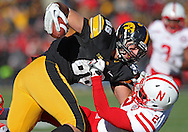 November 23 2012: Iowa Hawkeyes tight end C.J. Fiedorowicz (86) is pulled down by Nebraska Cornhuskers defensive back Alonzo Moore (2) after a catch during the second half of the NCAA football game between the Nebraska Cornhuskers and the Iowa Hawkeyes at Kinnick Stadium in Iowa City, Iowa on Friday November 23, 2012. Nebraska defeated Iowa 13-7 in the Heroes Game on Black Friday.