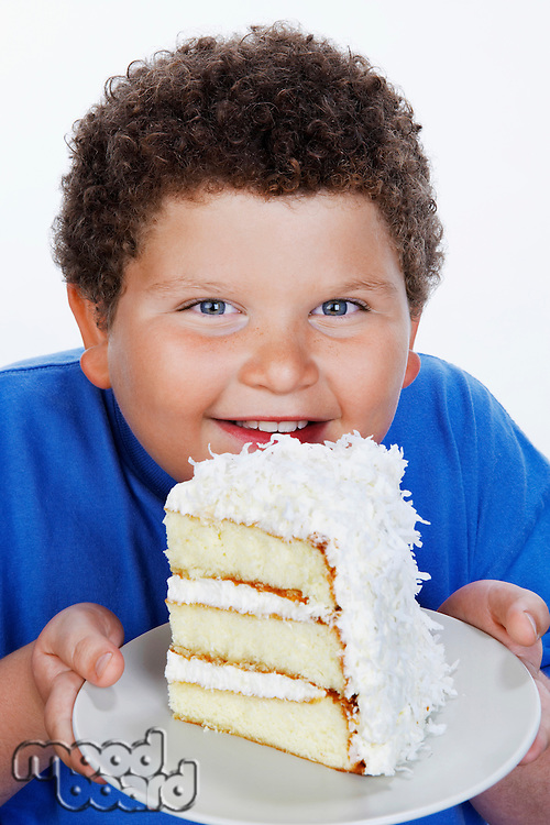 Overweight boy (13-15) holding Large Slice of Cake smiling portrait