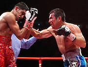 A battered and bloody Marco Antonio Barrera bleeds heavily whilst landing a right hand during the WBA and WBO Inter-Continental Lightweight title fight between Amir Khan and Marc Antonio Barrera at the MEN Arena on March 14, 2009 in Manchester, England.