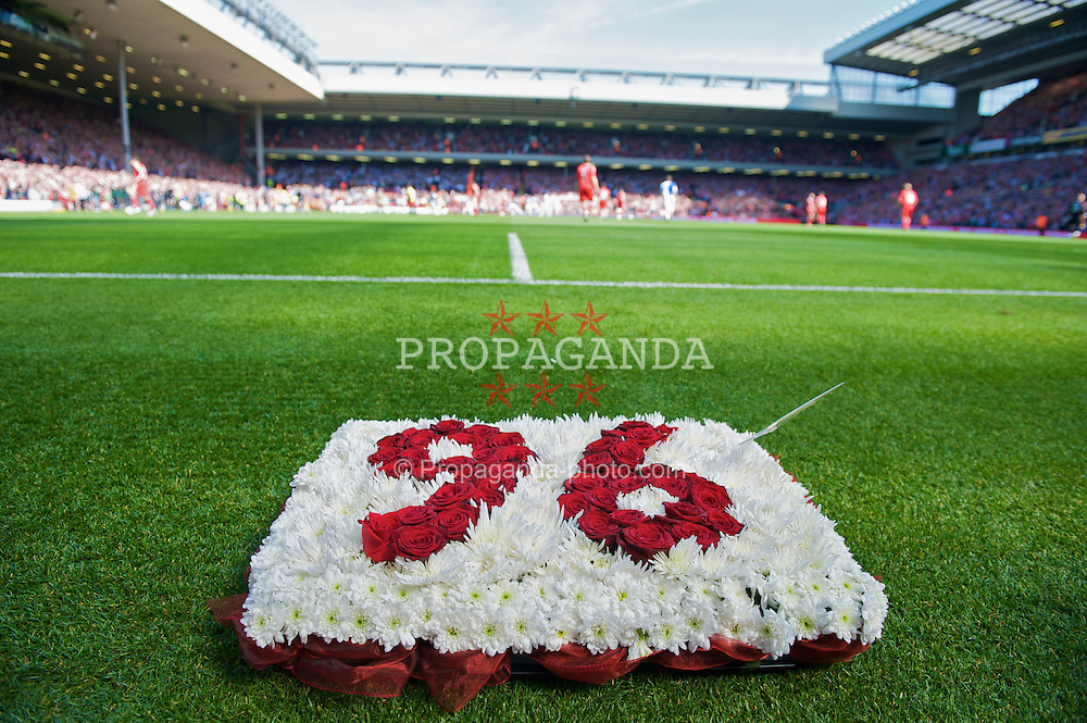 """LIVERPOOL, ENGLAND - Saturday, April 11, 2009: Blackburn Rovers' Stephen Warnock lays a wreath reading """"96"""" in front of the Spion Kop to mark the 20th anniversary of the Hillsborough disaster, in which 96 Liverpool fans lost their lives, before the Premiership match at Anfield. (Photo by: David Rawcliffe/Propaganda)"""