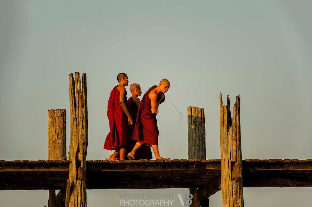 monks walking on the U Bein Bridge and spitting betel nut juice