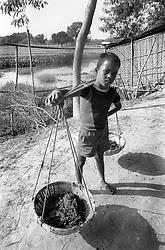 BANGLADESH UKHIA FEB95 - A young boy hauls two baskets of earth in rural Ukhia, southern Bangladesh...The Bangladesh Bureau of Statistics estimates the total working child population between 5 and 17 years old to be at 7.9 million...jre/Photo by Jiri Rezac..© Jiri Rezac 1994