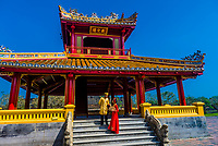 A Vietnamese couple wearing traditional costume, The Hue Citadel (a World Heritage site) was established by Emperior Gia Long in 1805. The huge fortress comprises three concentric enclosures-the Civic, Imperial and Forbidden Purple Cities., Hue, Central Vietnam.