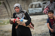 A woman carries her child while fleeing the recently liberated 17 Tammuz neighbourhood in west Mosul on 19 May, 2017.
