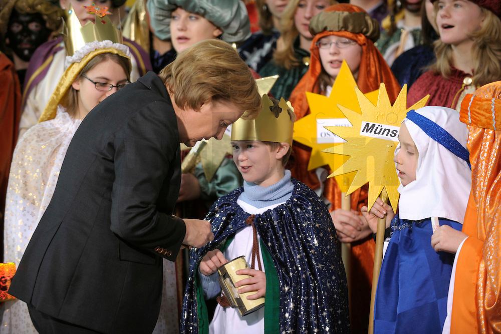 04 JUN 2008, BERLIN/GERMANY:<br /> Angela Merkel, CDU, Bundeskanzlerin, steckt ihre Spende in die Spendendose von einem der Heiligen drei Koenige, waehrend dem Empfang der Sternsinger im Bundeskanzleramt<br /> IMAGE: 20080104-01-029<br /> KEYWORDS: Heilige drei Koenige, Heilige drei Könige, spendet, Geld, Geldscheine, Kanzleramt