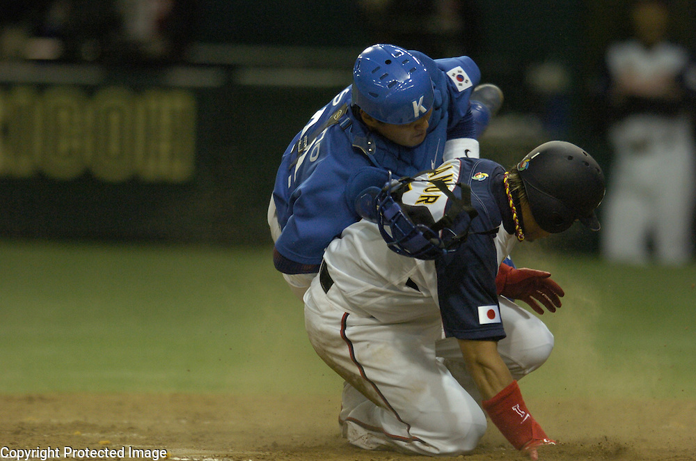 Team Japan's Akinori Iwamura is out at home plate on a force out tag by Team Korea's catcher In Sung Cho in the 4th inning in the Pool A Championship Game of the World Baseball Classic at Tokyo Dome, Tokyo, Japan.