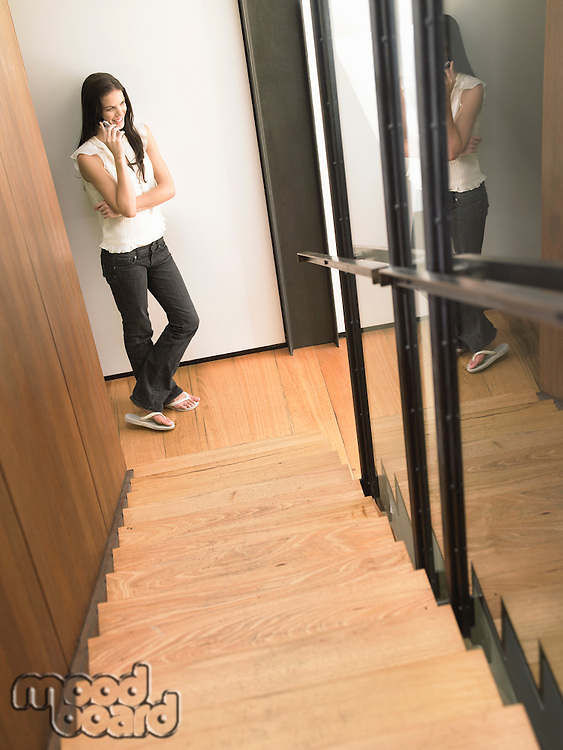 Young Woman on Cell Phone at Bottom of Stairs