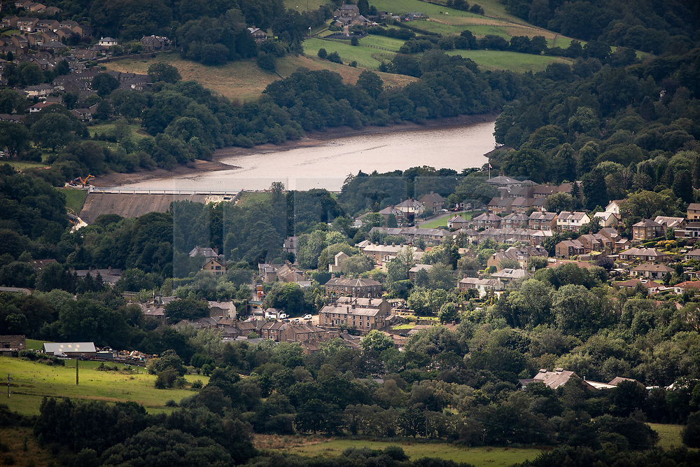 © Licensed to London News Pictures. 05/08/2019. Whaley Bridge, UK. GV of Whaley Bridge below the Toddbrook reservoir , illustrating the threat a failure of the reservoir's dam poses to the town below . The town of Whaley Bridge in Derbyshire remains evacuated after heavy rain caused damage to the Toddbrook Reservoir , threatening homes and businesses with flooding . Photo credit: Joel Goodman/LNP