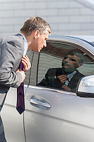Businessman adjusting tie while looking in car window