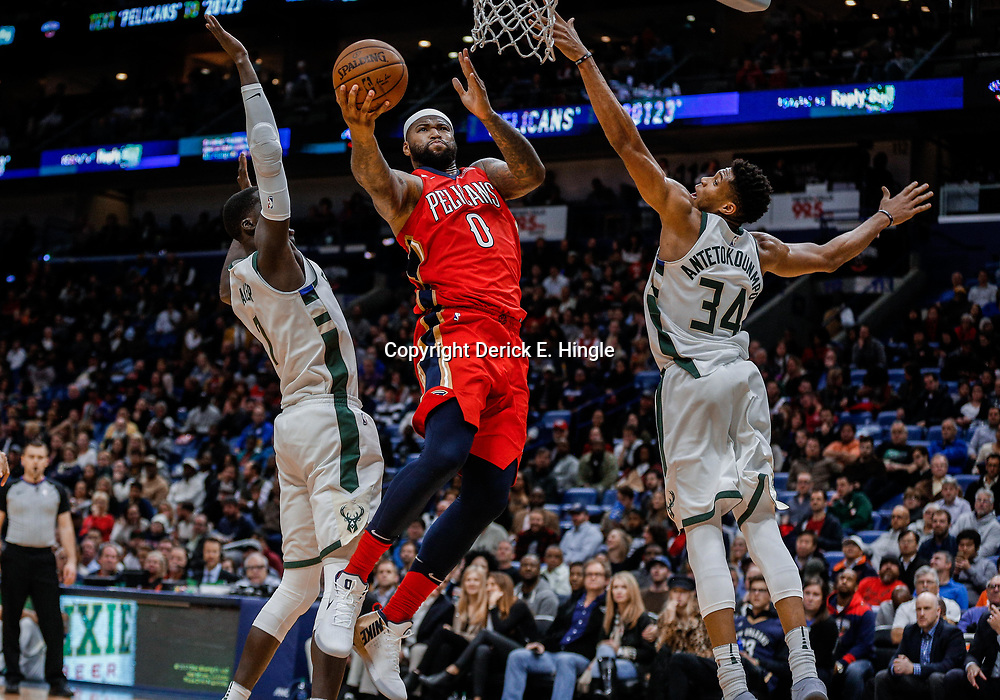 Dec 13, 2017; New Orleans, LA, USA; New Orleans Pelicans center DeMarcus Cousins (0) shoots between Milwaukee Bucks forward Giannis Antetokounmpo (34) and center Thon Maker (7) during the second half at the Smoothie King Center. The Pelicans defeated the Bucks 115-108. Mandatory Credit: Derick E. Hingle-USA TODAY Sports
