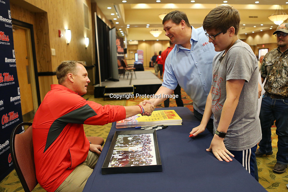 Ole Miss football head coach Hugh Freeze shakes hands with Mark Prince as his son Carson, 13, gets a photo signed by the coach Wednesday evening during the Rebel Roadshow at the BancorpSouth Conference Center.