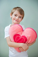 Portrait of little boy holding heart shape cushion