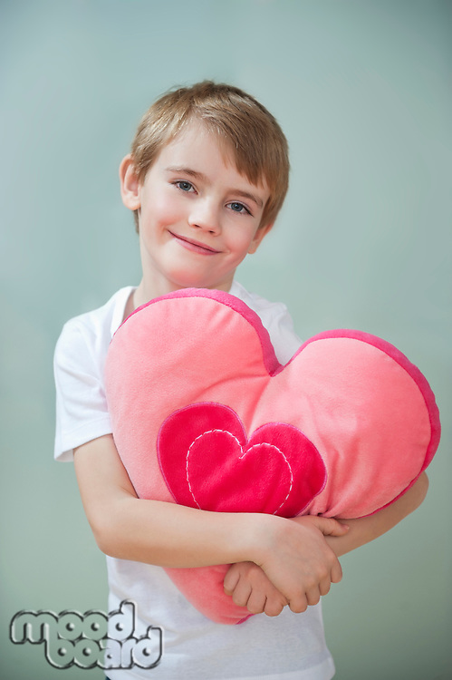 Portrait of little boy holding heart shape cushion