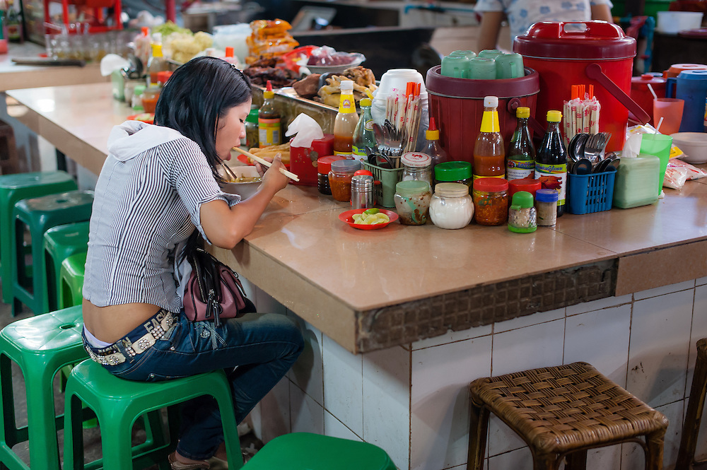 Girl eating at market restaurant counter in Siem Reap (Cambodia)
