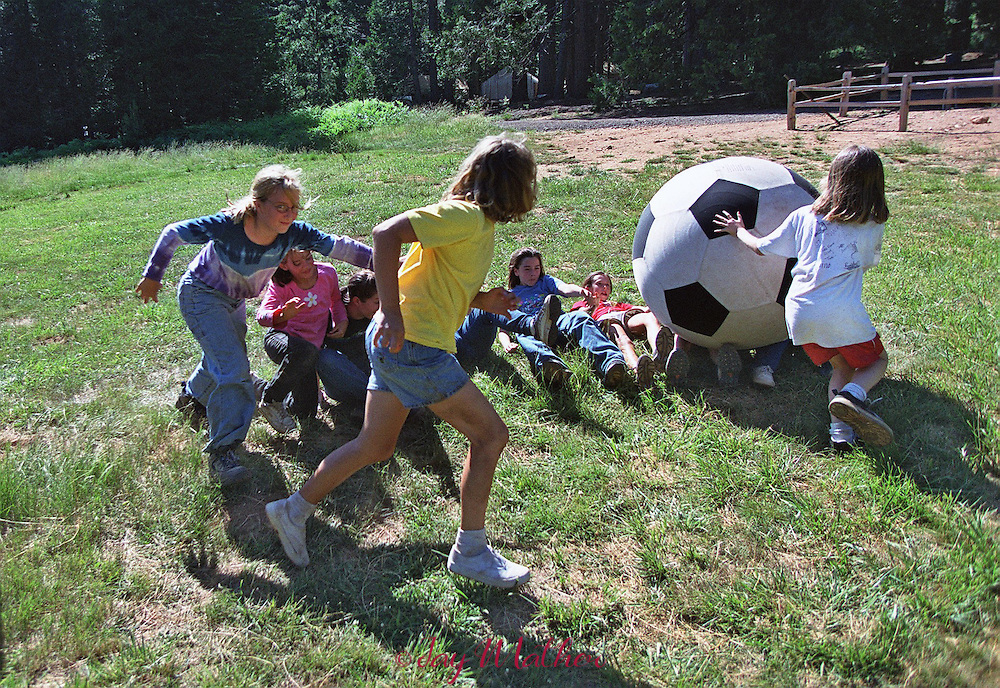 Campers race to get underneath a giant rolling soccer ball.  Meadow games are a part of the experience at Camp Menzies Girl Scout camp whre the girls are encouraged to form a group bond.  June 27, 2000.