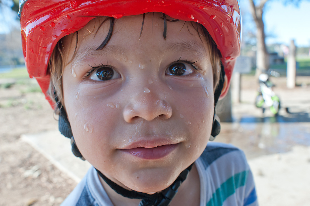 young boys face with red bycicle helmet, soaked with water