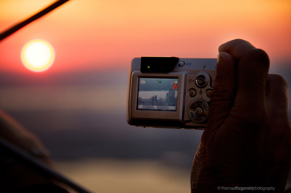 A tourist at the Empire State holds up his camera to take a picture of the sunset over the New York City Skyline