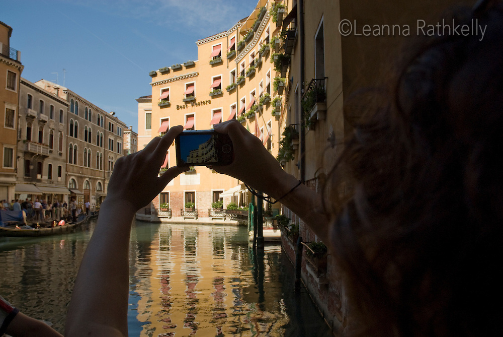 Teenage girl takes a picture of the Hotel Cavalletto along a canal in Venice, Italy.