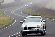 Porche Cayenne 4-wheel drive car drives along foggy road, Oxfordshire,  United Kingdom