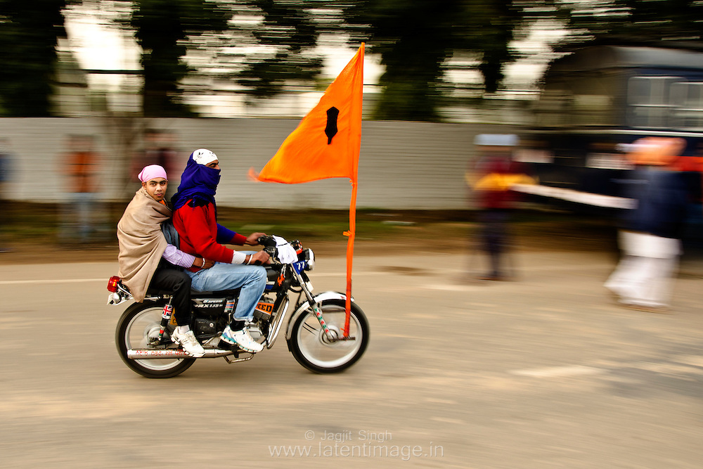 Sikh youth on motorbike with flag  which symbolises the strength and courage of Sikhism.