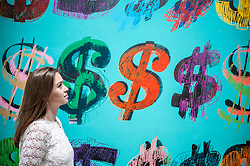 "© Licensed to London News Pictures. 08/06/2015. London, UK. A Sotheby's staff member looks at ""Dollar Signs"" by Andy Warhol (est. £4.5 - £6.5m), at the preview of ""To the Bearer on Demand"", a private collection of 21 works inspired by the US dollar, including Andy Warhol masterpieces, which will be auctioned on 1 and 2 July.  The collection is estimated to realise £50 million. Photo credit : Stephen Chung/LNP"