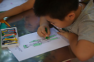 A young Vietnamese boy uses color pencils to draw, Vietnam, Southeast Asia