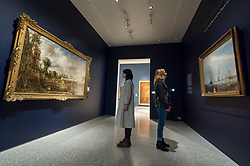 "© Licensed to London News Pictures. 11/01/2019. LONDON, UK. Staff members view ""The Opening of Waterloo Bridge ('Whitehall Stairs, June 18th, 1817')"" by John Constable (L) and ""Helvoetsluys"", 1832, by J.M.W. Turner (R) which are exhibited at The Royal Academy of Arts in Piccadilly for the first time since the artists clashed at the Summer Exhibition in 1832.  Turner allegedly added a small dab of red paint to his canvas, which he then converted into an image of a buoy floating in the sea. when he saw his painting next to Constable's.  The two works form ""He has been here and fired a gun"": Turner, Constable and the Royal Academy, on display from 12 January to 31 March 2019.  Photo credit: Stephen Chung/LNP"