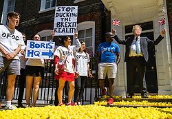 "© Licensed to London News Pictures. 27/06/2019. London, UK. Protesters spread yellow ducks across pavement outside a building believed to be the campaign headquarters for Boris Johnson's bid to become the next Leader of the Conservative Party. The protesters claim that Boris Johnson is ""ducking the Brexit reality"". Photo credit: Rob Pinney/LNP"