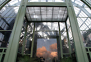 Tropical Rainforest Glasshouse (formerly Le Jardin d'Hiver or Winter Gardens), 1936, René Berger, Jardin des Plantes, Museum National d'Histoire Naturelle, Paris, France.  Low angle view of the glass and metal structure of the Art Deco main entrance which is reflecting the late afternoon clouds.
