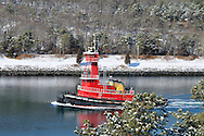 Winter scenic with red tugboat, water, snow and evergreen trees