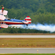 September 6, 2008 -- NAS BRUNSWICK, Maine. Wingwalker Ashley Battles of Tulsa, Oklahoma waves to the crowd while riding aboard Greg Shelton's 450 Stearman at The Great State of Maine Airshow. Shelton, of Collinsville, Oklahoma has been doing professional aerobatics since 1982. The airshow visited Naval Air Station Brunswick for the last time this weekend, bringing The U.S. Navy Blue Angels, The U.S. Army Golden Knights and a wide variety of static displays and interactive exhibits. The show drew over 150,000 people over three days with no mishaps among the performers and no emergencies among the attendees. .Because NAS Brunswick is scheduled to be closed in 2011 by the Base Realignment Commission, there will not be another Navy-sponsored airshow at this location. Yet, the Local Redevelopment Authority, responsible for managing the property after the departure of the Navy,  has included an airshow on a list of possible future uses for the property.  U.S. Navy Photo by Mass Communication Specialist 1st Class Roger S. Duncan (RELEASED)